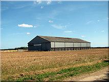 TF9038 : Large hangar in stubble field by Evelyn Simak