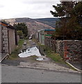SS9496 : Puddles on a lane in Cwmparc by Jaggery