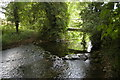 SP0701 : Ampney Brook and footbridge, behind Ampney St Mary church by Christopher Hilton