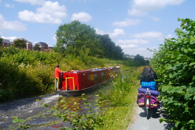 A cycle tourist passes a narrowboat on the Montgomery Canal