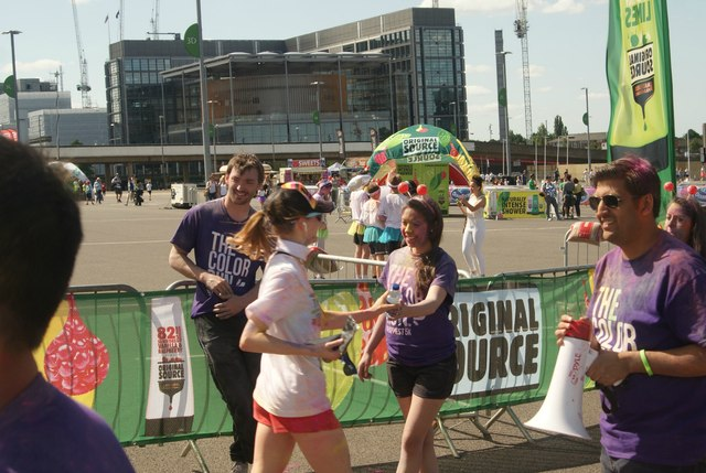 View of a Colour Runner taking a bottle of water at the finish line