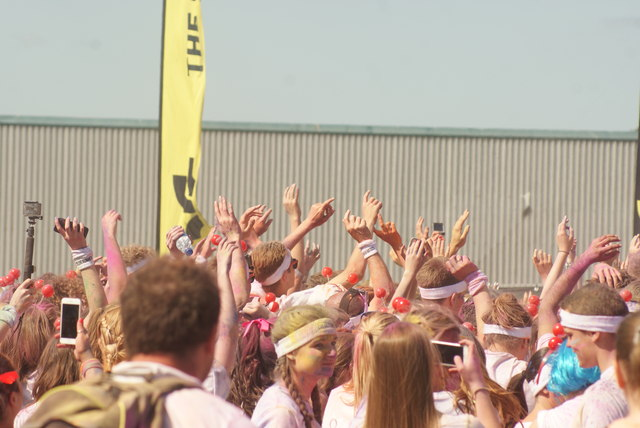 View of a sea of hands in the air at the Colour Run