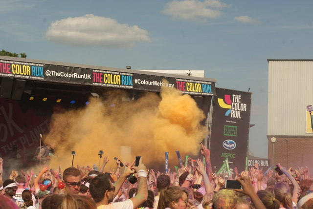 View of the presenter using a colour shooter at the Colour Run
