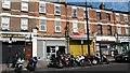 TQ4084 : Motorcycle parking and shops on Upton Lane by David Martin