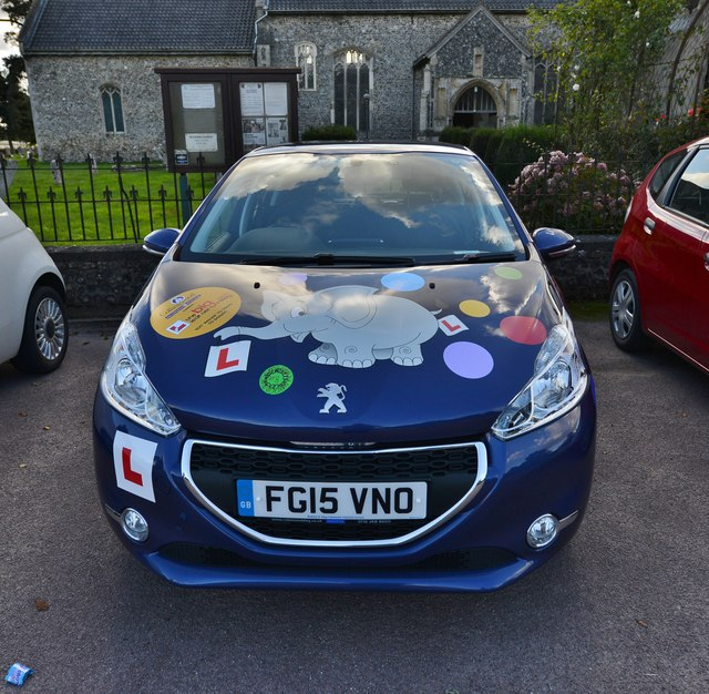 Roydon: St. Remigius Church: Learner driver car parked outside