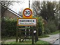 TL3758 : Hardwick Village Name sign on Main Street by Adrian Cable
