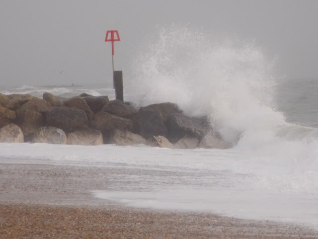 Hengistbury Head: a breakwater is hit by a wave