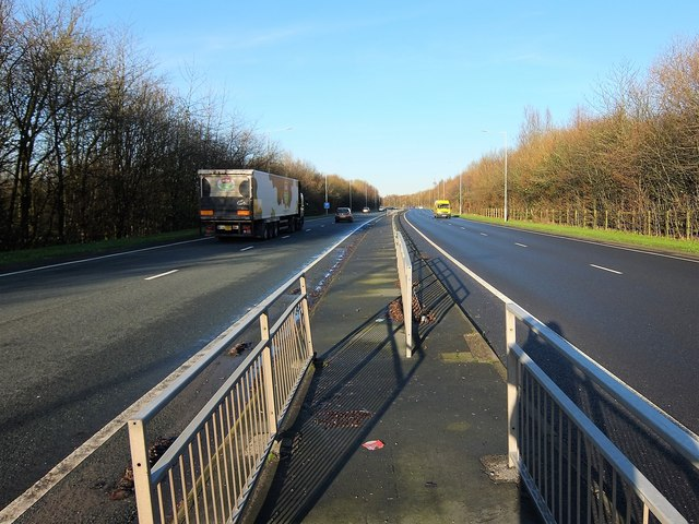 Looking north along the A6 London Way from a foot crossing