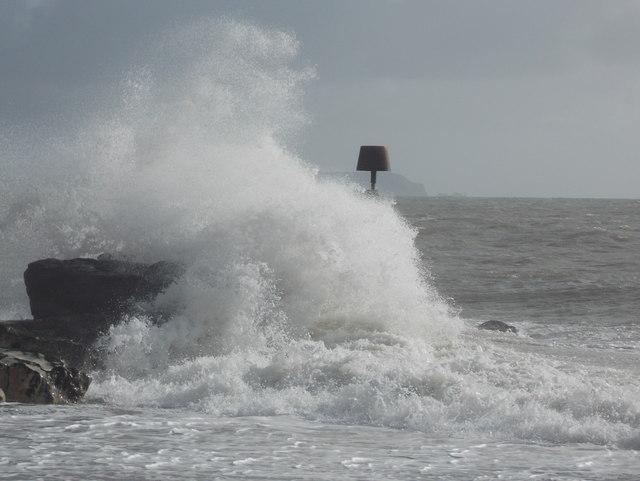 Hengistbury Head: a breakwater is hit by a wave
