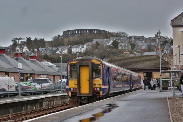 A Class 156 diesel train at Oban train station with McCaigs Tower in the background