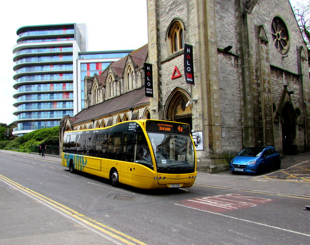 Yellow bus descends Exeter Road, Bournemouth