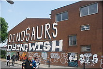 TQ3783 : View of Dinosaurs Dying Wish street art on Bream Street by Robert Lamb