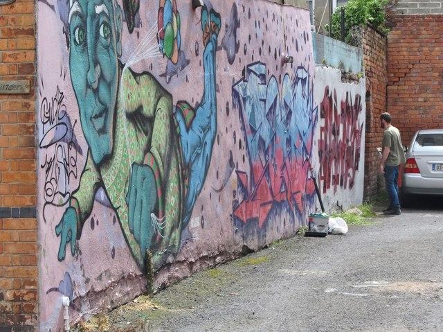 Mural artist at work off Bachelors Walk