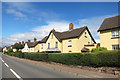SX9897 : Yellow Houses in Broadclyst by Des Blenkinsopp