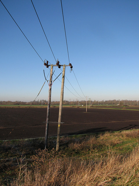 Blue sky, power lines and dark fen earth