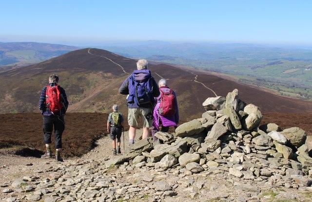 Walkers descending from the cairn on Moel y Gamelin