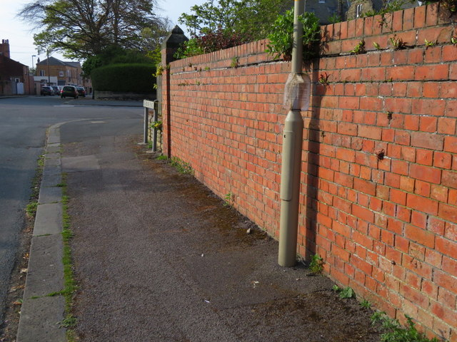 A wall in Belvedere Place, Scarborough and a bench mark