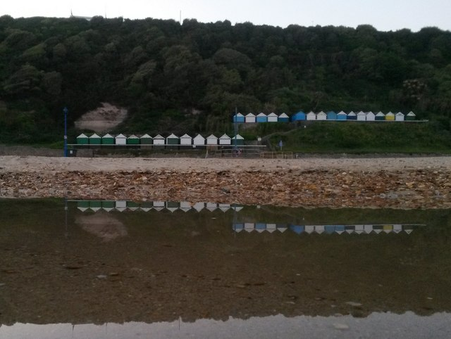 Bournemouth: some beach huts and the East Cliff are reflected