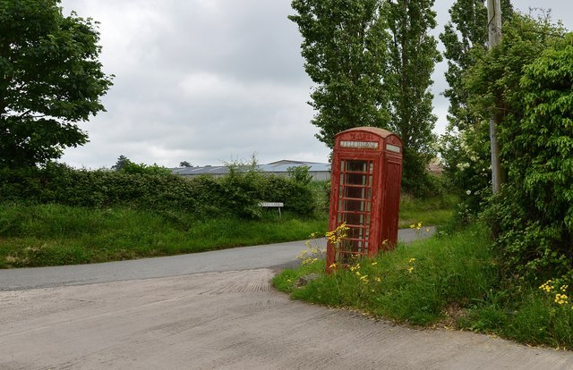 Besford: Telephone box, leaning, little used and in need of a coat of paint