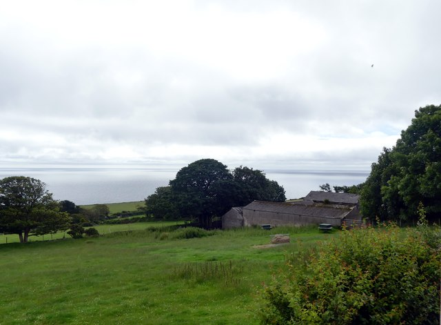 Fields and farm buildings with a sea view