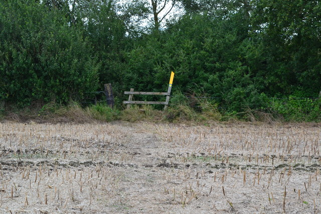 Stile and footpath marker on edge of stubble field