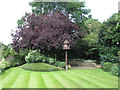 TQ2782 : The Holme, wooden dove house on pole in lawn by David Hawgood