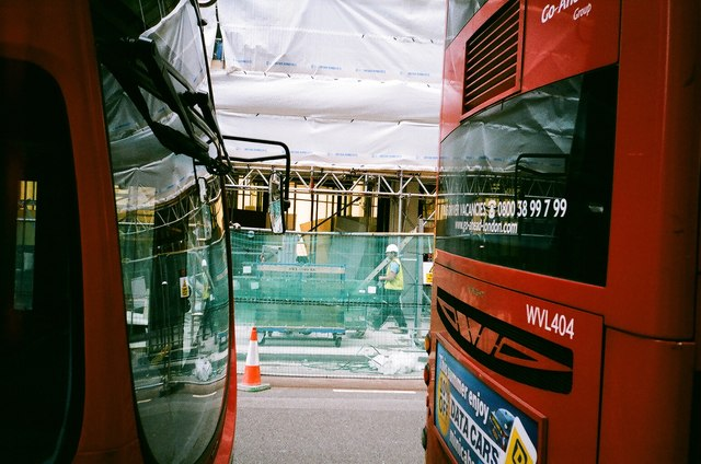 View of a building site on New Oxford Street framed by two buses