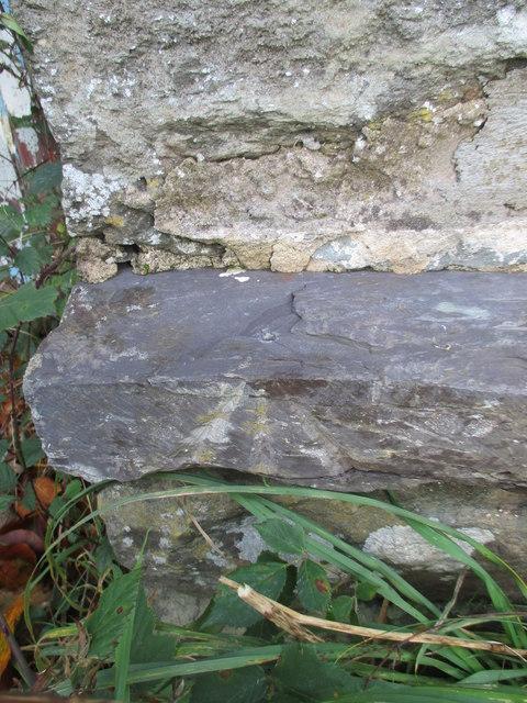 Damaged rivet benchmark on St Mary's Church Hall, Tregarth