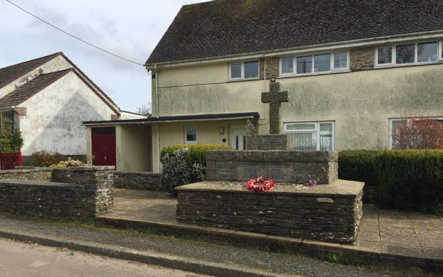 Blackawton War Memorial and a council house behind