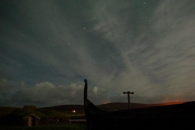 Viking longhouse and longship at Haroldswick, by moonlight