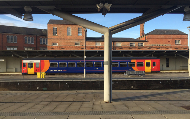 A single-carriage train drawing into Derby station