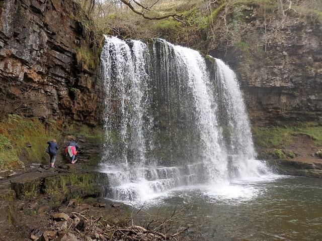 Walkers passing behind Sgŵd yr Eira