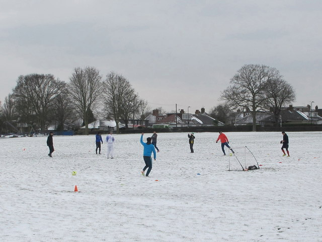 Informal football on snowy playing field, North Acton