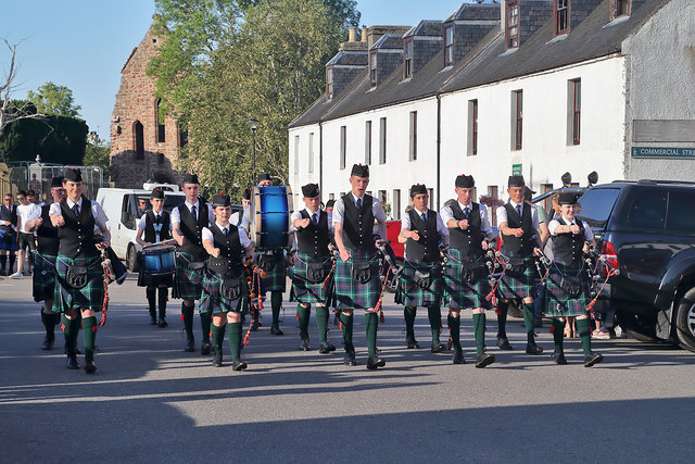 A marching pipe band in Beauly