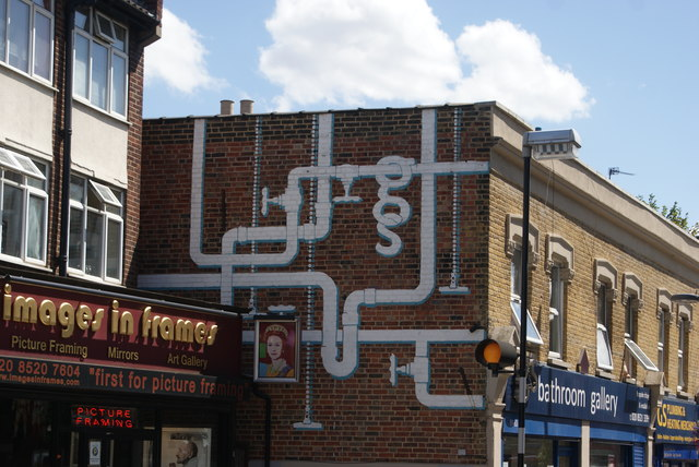 View of plumbing-themed street art on the side of Bathroom Gallery on Wood Street #2