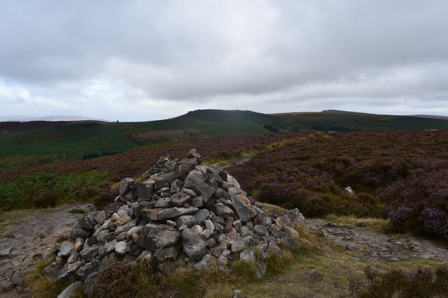 Large stone cairn at junction of paths.
