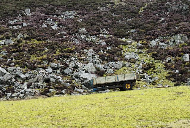 Farm trailer at foot of boulder slope