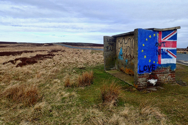 "Graffiti adorns the end of a disused concrete bus shelter on the East Cleveland Moors. On the left, the Eu flag, on the right, the Union flag. The word ""LOVE"" is spray-painted on the EU flag, and ""OUT NOW"" over the Union Jack."