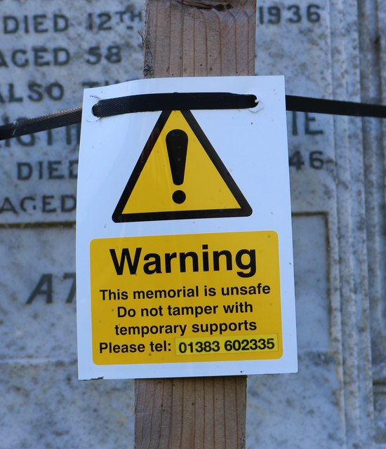 Warning sign on unstable headstone