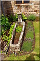 NZ1805 : Saxon coffin reused as a garden feature by Tiger
