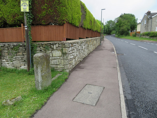 The B4226 Poolway Road and a defaced milestone