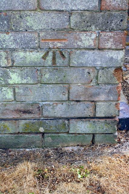 Benchmark on garage block on east side of Warminster Close