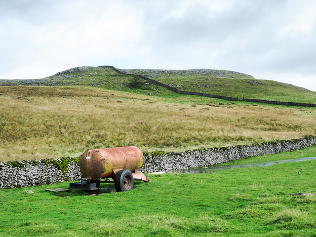 Dry stone wall with parked trailer tank
