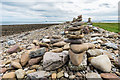 NU1441 : Stone piles by Ian Capper