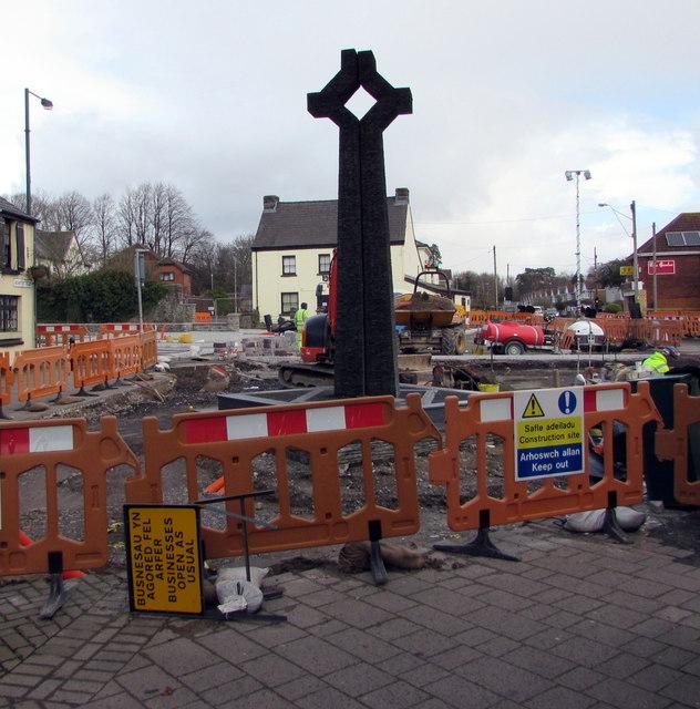 Temporary barriers enclosing the War Memorial Cross in Caldicot