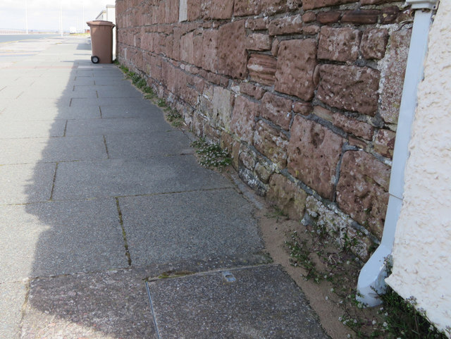 Sandstone wall with a bench mark in Meols Parade