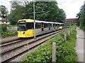SJ8590 : Metrolink tram leaving East Didsbury tram stop by Graham Hogg
