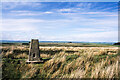 NY7659 : Moorland of Beacon Hill with trig point by Trevor Littlewood