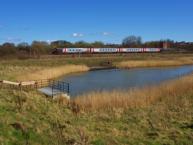 Cross Country train passing a pond in the Avenue Washlands