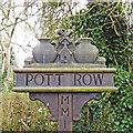 TF7021 : Pott Row village sign (detail) by Adrian S Pye